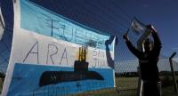A man hangs an Argentinian flag outside Argentina's Navy base in Mar del Plata, on the Atlantic coast south of Buenos Aires, on November 22.//AFP