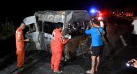 Officials examine the wreckage of a van that burst into flames following a crash in Sing Buri province early yesterday. The incident killed a Thai driver and all 13 Myanmar nationals.