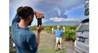 foreign tourist takes pictures in front of Mount Agung erupting seen from Kubu sub-district in Karangasem Regency, on Indonesia's resort island of Bali on Nov 27.//AFP