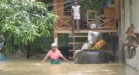 A woman wades through floodwater at her house in Trang on Saturday.