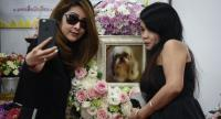 This photo taken on September 14, 2017 shows Pimrachaya Worakijmanotham (L) and her friend taking a selfie with a photo of Dollar, her six-year-old Shitzu dog, during the pet's funeral at Wat Krathum Suea Pla Buddhist temple in Bangkok.//AFP