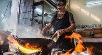 Supinya Junsuta, better known as Jay Fai, wears oversized goggles while cooking her signature dish of crabmeat omelette over charcoal, Her eatery is the only street food venue to have earned one Michelin star.