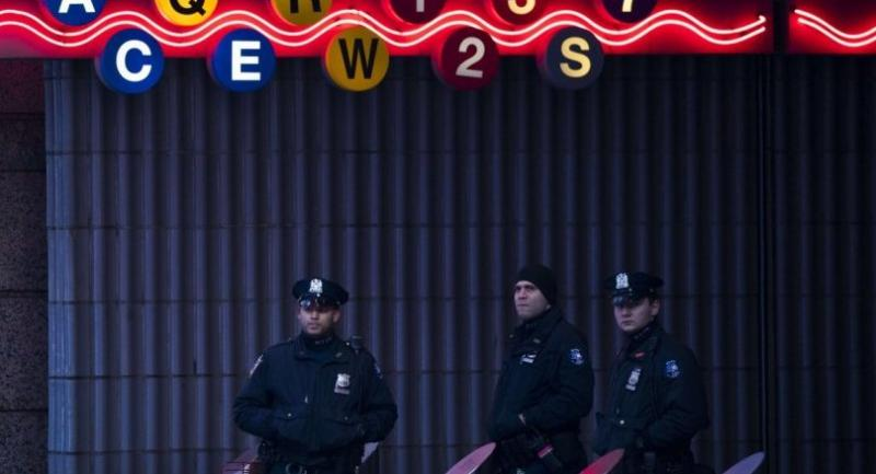 New York City Police Department officers stand guard at a closed subway station near Times Square and the New York Port Authority Bus Terminal, December 11 in New York City.//AFP