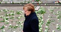 German Chancellor Angela Merkel walks past the memorial as she leaves the venue after the inauguration of the memorial for the victims of last year's deadly truck attack at the Christmas market at Breitscheidplatz in Berlin, on December 19, 2017.