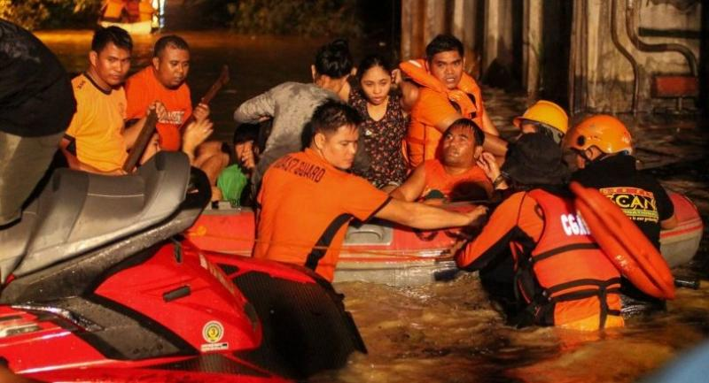 Rescue workers evacuate flood-affected residents in Davao on the southern Philippine island of Mindanao early on December 23, 2017, after Tropical Storm Tembin dumped torrential rains across the island./AFP