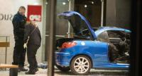 Police officers inspect damage in the lobby of the German Social Democratic Party (SPD) headquarters after a car was used to ram the building early December 25.//AFP