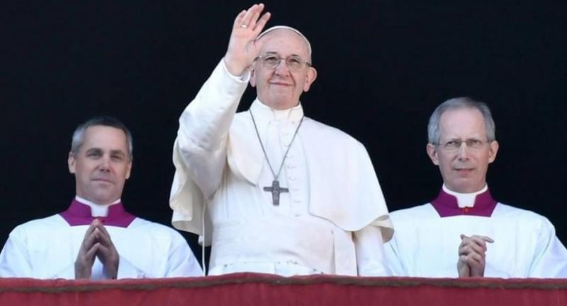 Pope Francis (C) waves from the balcony of St Peter's basilica during the traditional