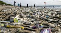 People walk next to piles of plastic debris brought in by strong waves on Kuta beach, Bali's best-known tourist destination, Indonesia, 15 December 2017. EPA-EFE