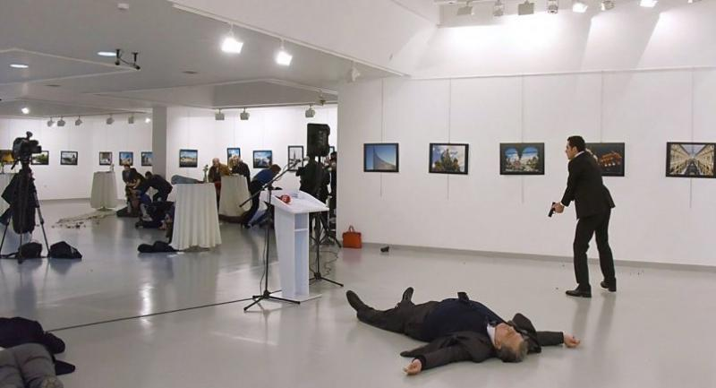 (FILES) This file photo taken on December 19, 2016 shows Andrei Karlov (2R), the Russian ambassador to Ankara, lying on the floor after being shot by Mevlut Mert Altintas (R) during an attack during a public event in Ankara.  / AFP PHOTO