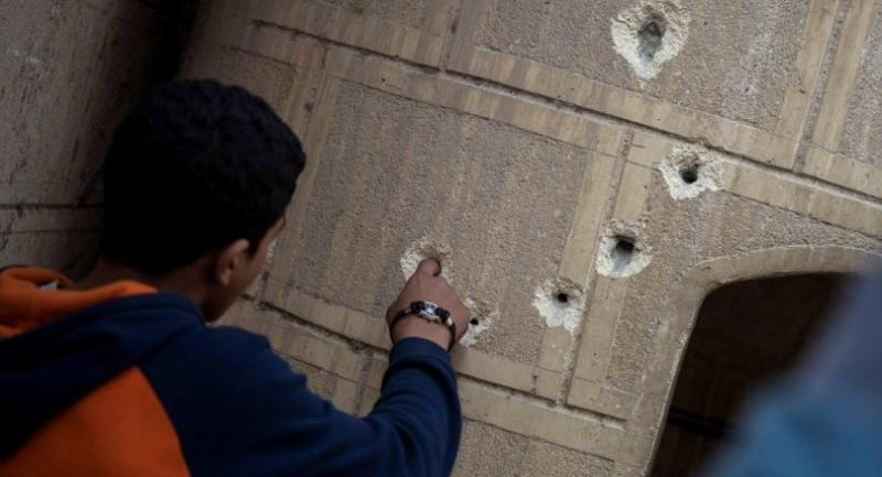 A man points at bullet holes on a construction outside Mar Mina church following an attack on the church in the district of Helwan, southeastern Cairo, Egypt, 29 December 2017. // EPA-EFE PHOTO