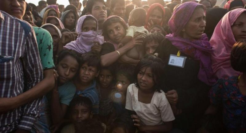 In a photo taken on November 28, 2017, Rohingya women and children gather to collect aid at the Kutupalong refugee camp in Cox's Bazar.//AFP