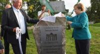 German Chancellor Angela Merkel (R) and member of the parliament Eckhardt Rehberg unveil a memorial dedicated to the German Unification and to former German Chancellor Helmut Kohl during an election campaign event on August 31, 2017 in Tellow./AFP