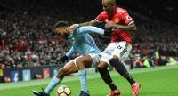 Manchester City's English midfielder Raheem Sterling (L) tries to shield the ball from Manchester United's English midfielder Ashley Young (R) during the English Premier League football match between Manchester United and Manchester City.