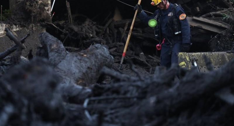 Los Angeles County urban search and rescue worker searches a pile of debris for victims of a mudslide on January 11, 2018 in Montecito, California. // AFP PHOTO