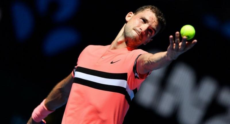 Bulgaria's Grigor Dimitrov serves against Austria's Dennis Novak during their men's singles first round match on day one of the Australian Open tennis tournament in Melbourne on January 15, 2018. / AFP PHOTO