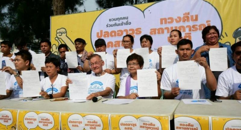 Representatives from over twenty civil society groups yesterday hold up signing forms to petition for a bill to revoke 35 of the junta's announcement and orders