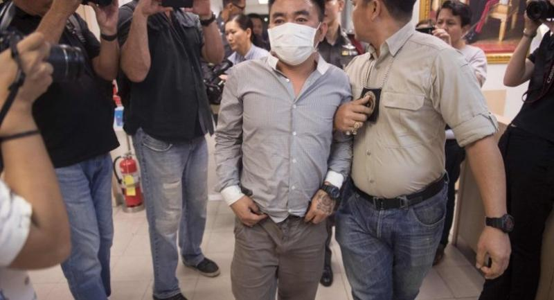 Boonchai Bach (C), 40, a Vietnamese national with Thai citizenship and alleged kingpin in Asia's illegal trade in endangered species, is escorted past journalists as he is processed at a police station in Bangkok on January 20, 2018. /AFP