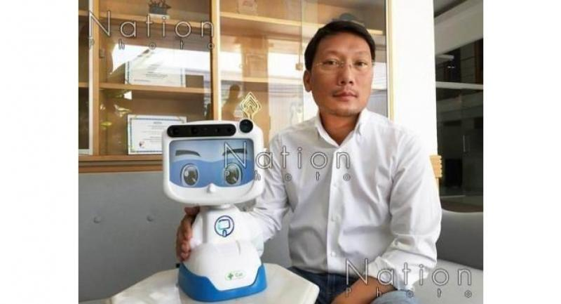 Chalermpon Punnotok, founder and chief executive officer of CT Asia Robotics Co Ltd, shows off the Dinsow mini robot, one of the models designed to help take care of old people.