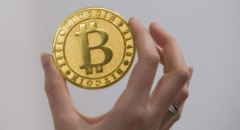 A person holds on January 17, 2018 shows a visual representation of the digital cryptocurrency Bitcoin, at La Maison du Bitcoin in Paris. / AFP PHOTO / GEOFFROY VAN DER HASSELT