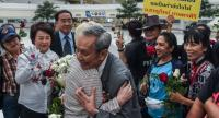 Esteemed historian Charnvit Kasetsiri, a former rector of Thammasat University, turned himself in to police at Chaengwattana Government Centre yesterday afternoon.