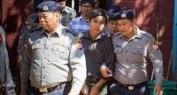 File phoro: Myanmar police officers escort Reuters journalists Wa Lone (back C) and Kyaw Soe Oo (C) at the northern district court in Yangon on January 23, 2018. // AFP PHOTO