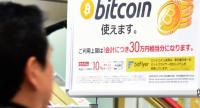 A man walks past a poster that informs customers that bitcoin can be used in this shop in Tokyo on January 06, 2018. /AFP