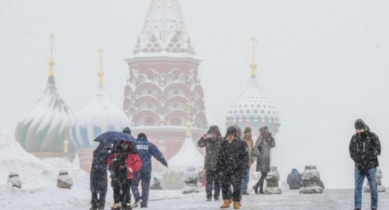 People walk on the snow covered Red Square in front of Saint Basil's Cathedral during a heavy snowfall in Moscow on January 31, 2018. / AFP PHOTO