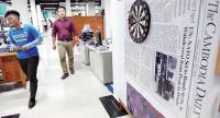 Cambodia Daily staffers walk past a blown up first edition in office last September, days before the paper was forced to close. //AFp