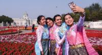 "Women in traditional Thai costumes yesterday pose for a selfie with the Anantasamakhom Throne Hall in the background at the venue for the winter festival event of ""Oon Ai Rak Klay Kwam Nao"". Photo Chalinee Thirasupa"