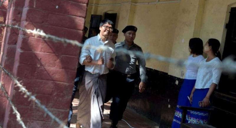 Detained Myanmar journalist Wa Lone (L) is escorted by police to a court in Yangon to face trial on February 6, 2018. // AFP PHOTO