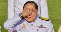 This December 4, 2017 photo shows the ruling junta's second-in-command, Deputy PM General Prawit Wongsuwan, covering his eyes while displaying a watch he is wearing during a photo call with other members of a new cabinet in Bangkok. / AFP PHOTO