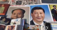 Posters of Chinese President Xi Jinping (R) and late communist leader Mao Zedong are seen at a market in Beijing on February 26.//AFP
