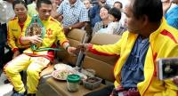 Srisaket Sor Rungvisai receives a grilled paddy field rat, his favourite Isaan delicacy, from his father Jiamsak, on his return to Bangkok yesterday.