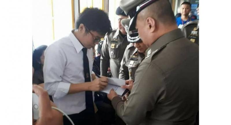 Student activist Netiwit Chotiphatphaisal signs his co-translated book for Deputy Police Commissioner Pol Gen Srivara Ransibrahmanakul (courtesy of Facebook page Netiwit Ntw)