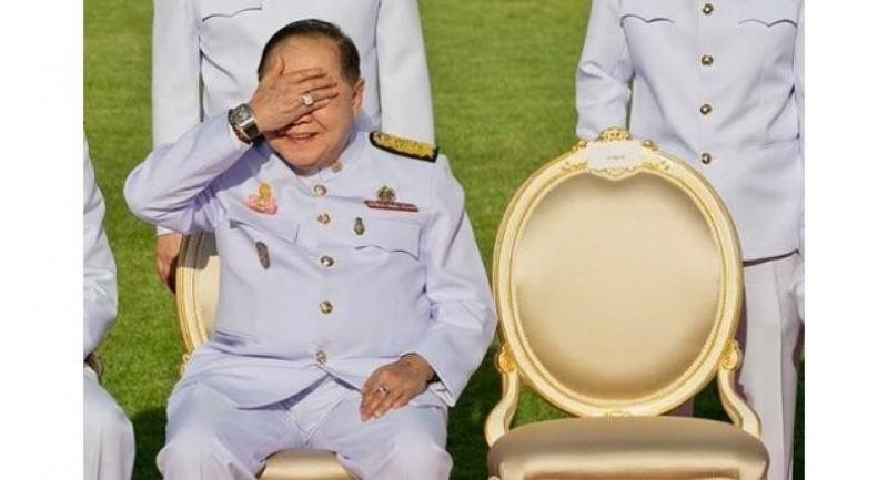 Deputy Prime Minister General Prawit Wongsuwan covers his eyes, displaying a luxury watch and a ring, during a photo call with other members of a new Cabinet in Bangkok in December. / AFP