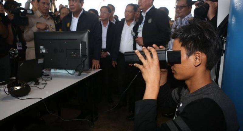 Prime Minister General Prayut Chan-o-cha observes a demonstration of a retina-scanning machine, which is used to help to verify the nationalities of migrant workers, during his field visit to Samut Sakhon yesterday.