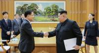 This handout from the presidential Blue House taken on March 5, 2018 shows North Korean leader Kim Jong Un (R) shaking hands with South Korean chief delegator Chung Eui-yong (L). // AFP PHOTO