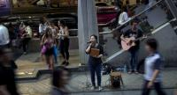 This photo taken on February 5, 2018 shows a blind singer performing in front of a skytrain station in Bangkok. // AFP PHOTO