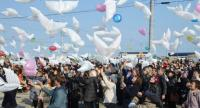 Residents fly dove-shape balloons to mourn victims of the 2011 tsunami and earthquake disaster at Natori in Miyagi prefecture on March 11.//AFP