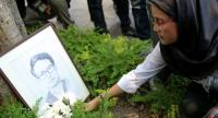 Angkhana Neelapaijit, the wife of missing human rights lawyer Somchai Neelapaijit, lays flowers in front of his picture on the 14th anniversary of his disappearance, at Thammasat University's Faculty of Law yesterday.