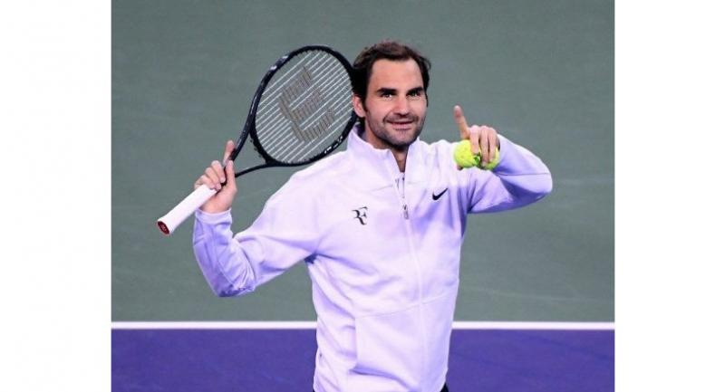 Roger Federer of Switzerland celebrates his win over Hyeon Chung of South Korea by tossing by hitting tennis balls into the crowd during the BNP Paribas Open at the Indian Wells Tennis Garden on March 15, 2018 in Indian Wells.