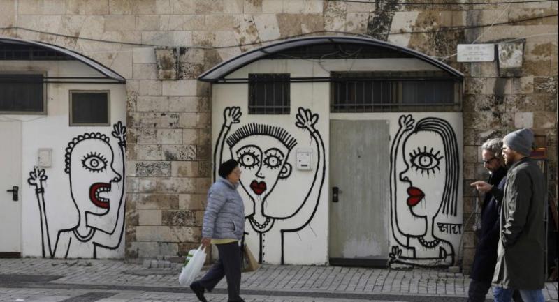 People walk past drawings by New York-based Israeliborn street artist Sara Erenthal in the Israeli city of Tel Aviv. / AFP