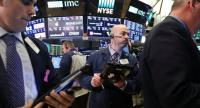 Traders work the floor of the New York Stock Exchange after the Federal Reserve raised its benchmark interest rate on Wednesday. The benchmark Dow Jones Industrial Average shed 44 points at the end of the day. --Getty Images/AFP