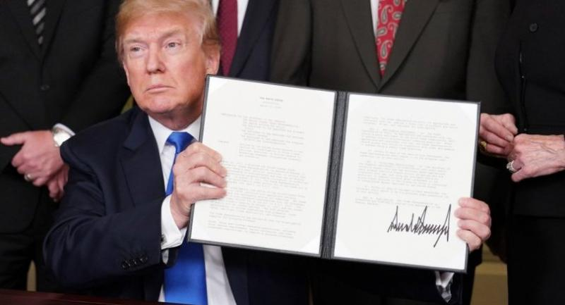 US President Donald Trump signs trade sanctions against China on March 22, 2018, in the Diplomatic Reception Room of the White House in Washington, DC, on March 22, 2018./AFP