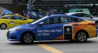 A Comfort Delgro taxi with an advertisement offering services on Uber apps ride through the street in Singapore on March 26, 2018./AFP