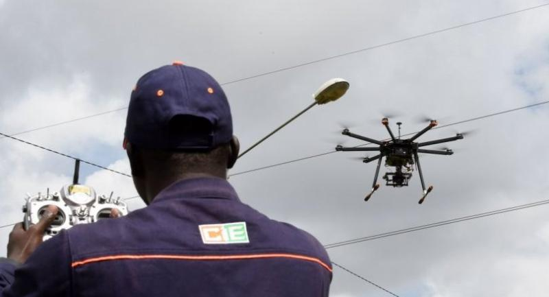 An employee of Ivorian Electricity Co pilots a drone from the Electricity Professional Centre to monitor the highvoltage electric network./AFP