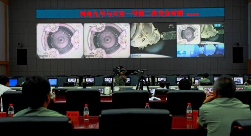 In this file photo taken on June 24, 2012 shows Chinese technicians at the Jiuquan Space Centre monitor the Shenzhou-9 spacecraft./AFP