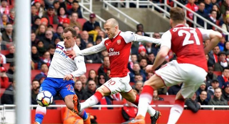 Arsenal's English midfielder Jack Wilshere (C) shoots past Stoke City's Swiss forward Xherdan Shaqiri (L) during the English Premier League football match between Arsenal and Stoke City at the Emirates Stadium in London on April 1, 2018.
