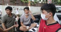 Warut (red shirt) sits with his friend after escaping the fire from his apartment building on Tuesday.