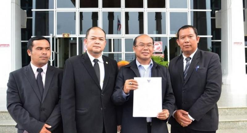 Preecha (2nd from right) stands with his lawyers after filing complaint with a Court in Kanchanaburi province on Thursday.